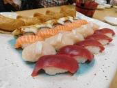 Sushi, in order: tuna, scallop, salmon, & eel, & bean curd dumplings.