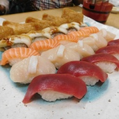 Sushi, in order: tuna, scallop, salmon, & eel, & bean curd dumplings.