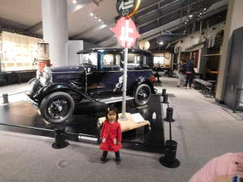 A toddler caught everyone's camera while standing in front of one of the first autos imported to Tokyo from England.
