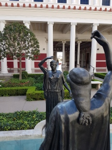 The peristyle garden features Roman sculptures.