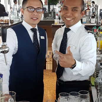 Smiling bartenders with generous pours.