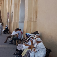 Elderly men sit idly along the streets.