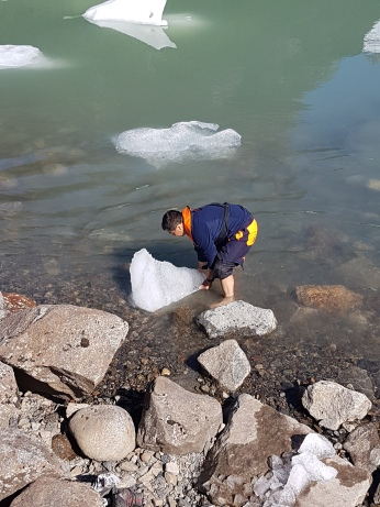 A ship crewman wades in the freezing waters to grab an iceberg